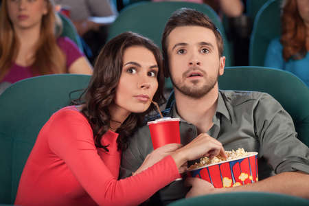 Great movie! Young couple eating popcorn and drinking soda while watching movie at the cinema photo