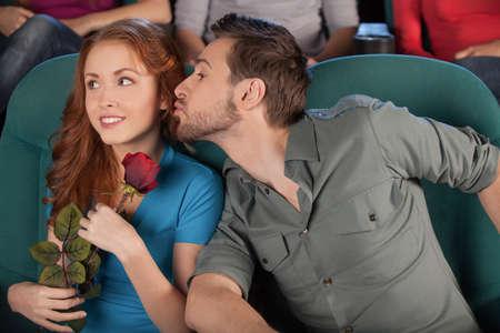 hombres besandose: Tratando de darle un beso. Hombres jovenes hermosos tratando de besar a su novia mientras ve la pel�cula en el cine Foto de archivo