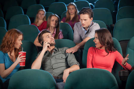 Stop talking! Young men talking at phone while watching movie at the cinema photo