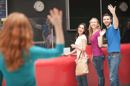 Friend� meeting at the cinema. Cheerful young people greeting their friend at the cinema box office photo