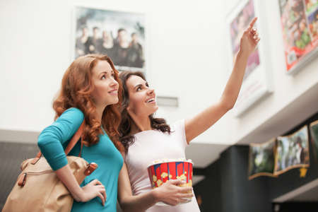 Friends choosing movie at the cinema. Beautiful young female friends choosing movie to see at the cinema