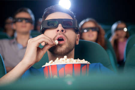 eating popcorn: Men at the cinema. Excited young men in glasses watching movie at the cinema and eating popcorn Stock Photo