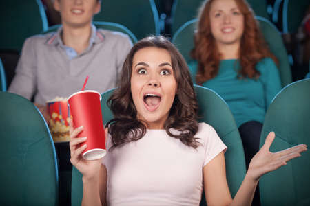 Excited women at the cinema. Beautiful young women drinking soda and gesturing while watching movie at the cinema photo