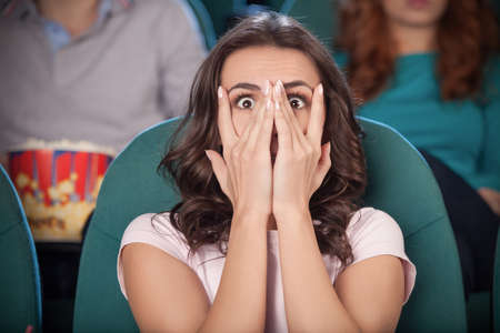 Watching  horror movie. Terrified young women covering her face with hand while watching movie at the cinema photo
