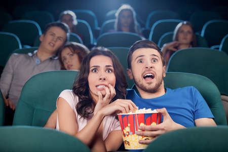 Couple watching horror movie. Terrified people in watching movie at the cinema photo
