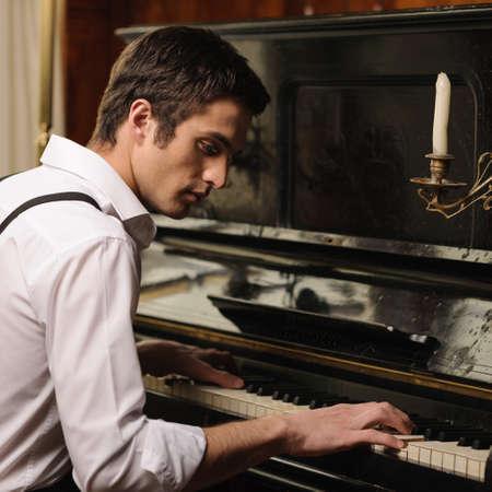 tocando el piano: Hacer m�sica. Perfil de un hombre joven hermoso que toca el piano