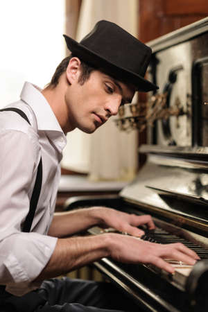 Virtuoso playing piano. Side view of handsome young men playing piano photo