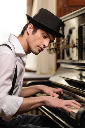 tocando piano: Virtuoso tocando el piano. Vista lateral de apuestos jóvenes tocando el piano