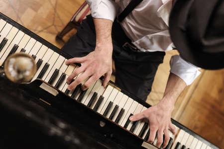 tocando piano: El talento y virtuosismo. Vista superior de los hombres j�venes y apuestos tocando el piano