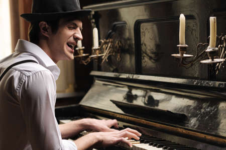 He� got creative soul. Handsome young men playing piano and singing photo