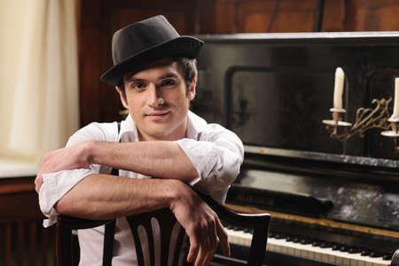 영감을 기다리고 있습니다. 그의 피아노 앞에 앉아 잘 생긴 젊은 남자의 초상화