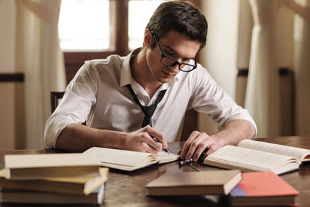 creative writer: Writer at work. Handsome young writer sitting at the table and writing something in his sketchpad