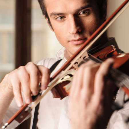young musician: Young virtuoso. Portrait of handsome young musician playing the violin