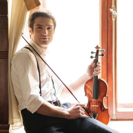 only adult: Musician and the violin. Handsome young men sitting on the windowsill and holding the violin