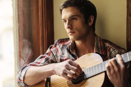 practicing: He loves the guitar sounds. Handsome young men sitting on the windowsill and playing guitar Stock Photo