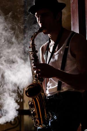 ジャズは彼の人生です。ハンサムな若い jazzmen 背景に煙がサックスを演奏