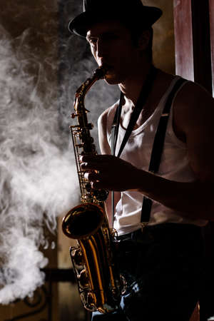 saxophonist: Jazz is his life. Handsome young jazzmen playing sax with a smoke on the background