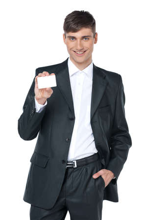 Young smiling business man handing a blank business card. Standing over white background photo
