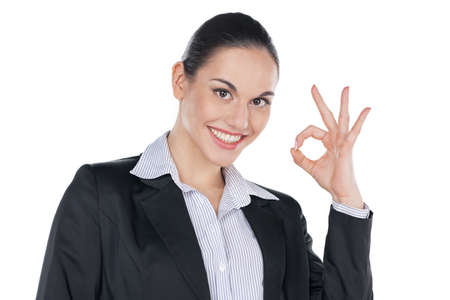 Portrait of Smiling businesswoman with ok gesture. Standing isolated on white photo