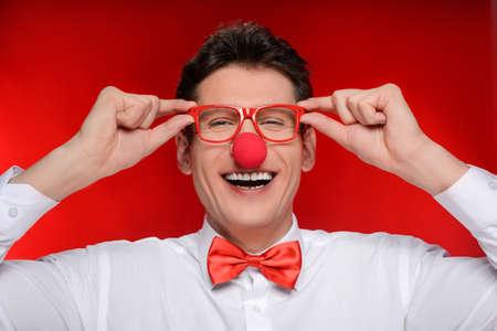 nariz roja: Payaso en gafas. Hombre alegre con nariz de payaso tocando sus anteojos mientras está de pie aislado en rojo Foto de archivo