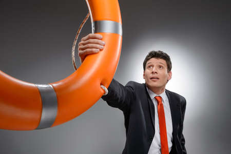 life buoy: Help is at hand  Worried businessman grabbing a life belt while isolated on gray