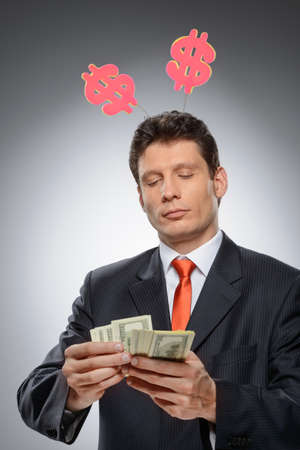 moneymaker: Money-maker  Funny businessman with a dollar hornes on the head counting money against grey background