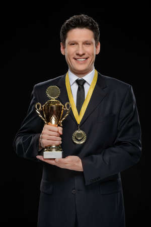 Business winner. Happy businessman holding a trophy while standing against black background photo