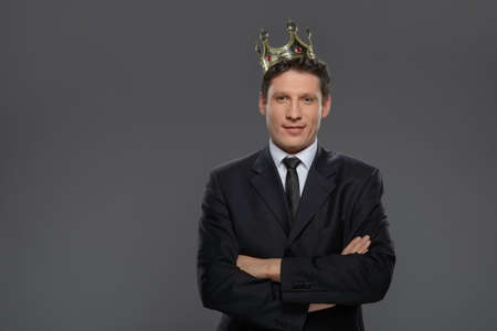 crown king: Business king. Confident businessman in crown standing isolated on gray with his arms crossed