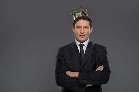 corona rey: Rey de negocios. Hombre de negocios conf�a en la corona de pie aislado en gris con los brazos cruzados