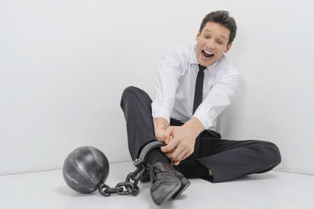 shackles: Trying to get freedom  Shocked businessman sitting on the floor with shackles chained to his legs Stock Photo