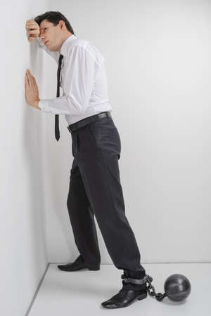 No more freedom  Full length of depressed businessman standing with shackles chained to his legs photo