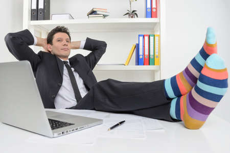 Businessman in funky socks  Confident businessman holding his legs in funny socks on the desk photo