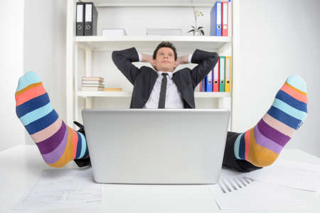 working place: Funky socks  Happy businessman in funky socks sitting at his working place and holding head in hands