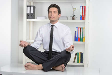 No stress Confident businessman sitting on the office desk and meditating with his eyes closed Stock Photo