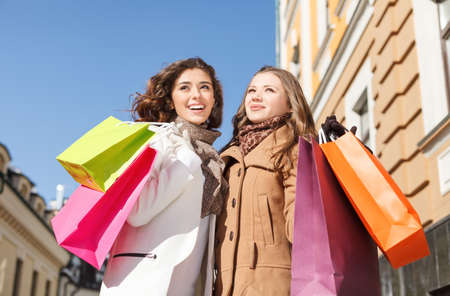 Friends shopping. Low angle view of happy two young women standing with their hands raised and holding the shopping bags photo