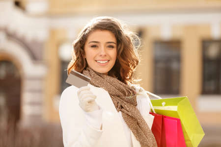 gift bag: Shopping made easy! Beautiful young women holding a credit card in one hand and the shopping bags In another one Stock Photo