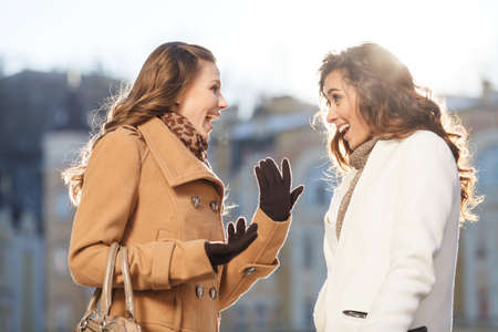 two people talking: Girls gossiping. Two beautiful young women gossiping while standing outdoors Stock Photo