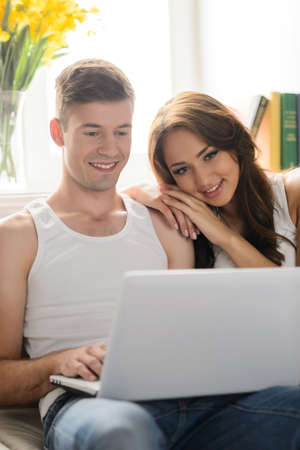 surfing the web: Surfing web together. Beautiful young couple sitting close to each other and reading books Stock Photo