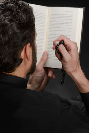 Reading the Holy Bible. High angle view of beard man reading the Holy Bible and holding a rosary beads in his hand photo