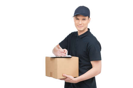 Confident deliveryman at work. Cheerful young deliveryman holding a cardboard box with a clipboard on it and smiling while isolated on white