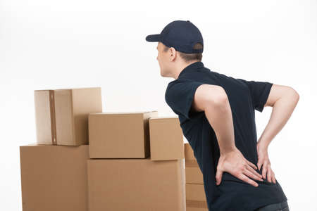 back shot: Backache. Young deliveryman standing with his hands on back and feeling pain