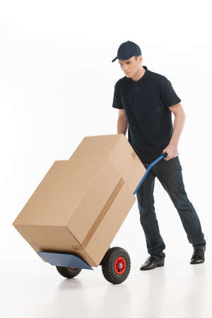 Moving house. Full length of young deliveryman with a hand truck transporting the cardboard boxes photo