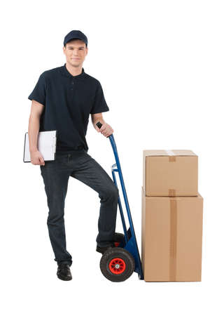 hand truck: Box moving. Cheerful young deliveryman leaning on the cart with boxes on it while isolated on white Stock Photo