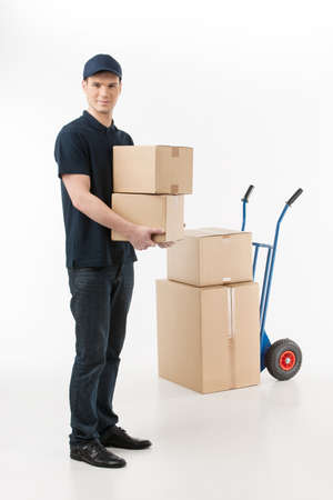 hand truck: Moving boxes. Full length of young deliveryman holding a stack of boxes with a hand truck on the background