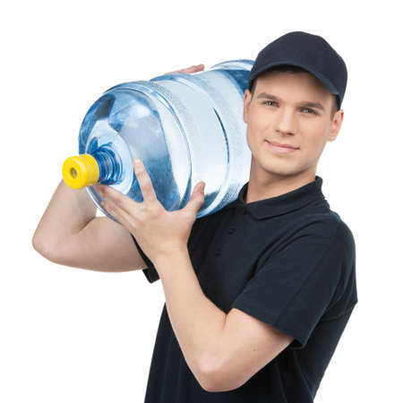 water transportation: Water delivery. Cheerful young deliveryman holding a water jug while isolated on white