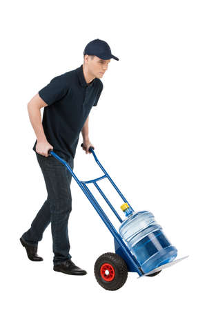 hand truck: Delivering water. Cheerful young going carrying a hand truck with water jug on it while isolated on white