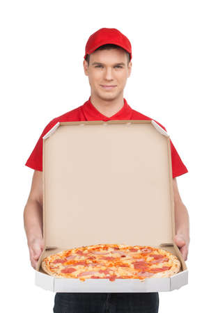 Pizza delivery. Cheerful young deliveryman holding a pizza box while isolated on white photo