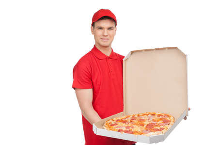 pizza box: Our best pizza for you. Young cheerful pizza man holding an open pizza box and smiling while isolated on white Stock Photo