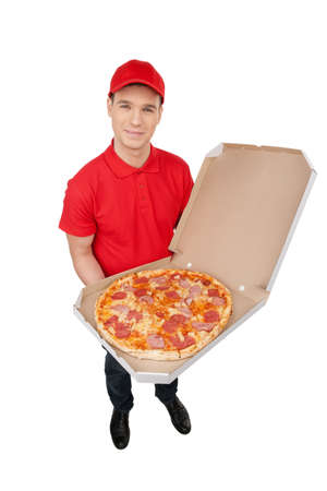 deliveryman: Delivering pizza. Top view of cheerful young deliveryman holding a pizza box while isolated on white Stock Photo