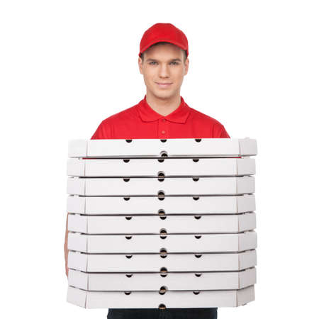 Your pizza! Young cheerful pizza man holding a stack of pizza boxes and smiling while isolated on white photo